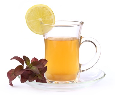 Cup of herbal tea with red tulsi leaves and lemon
